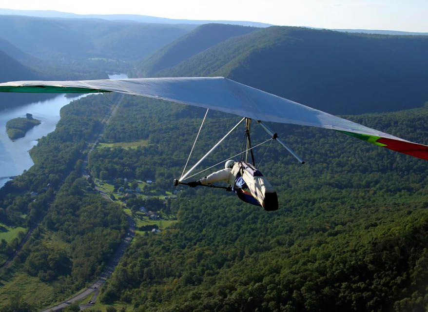 Man Hang Gliding Over Wooded Area